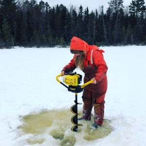 Emily Whitaker drills a hole in the ice on South Sparkling bog. Photo: Hilary Dugan